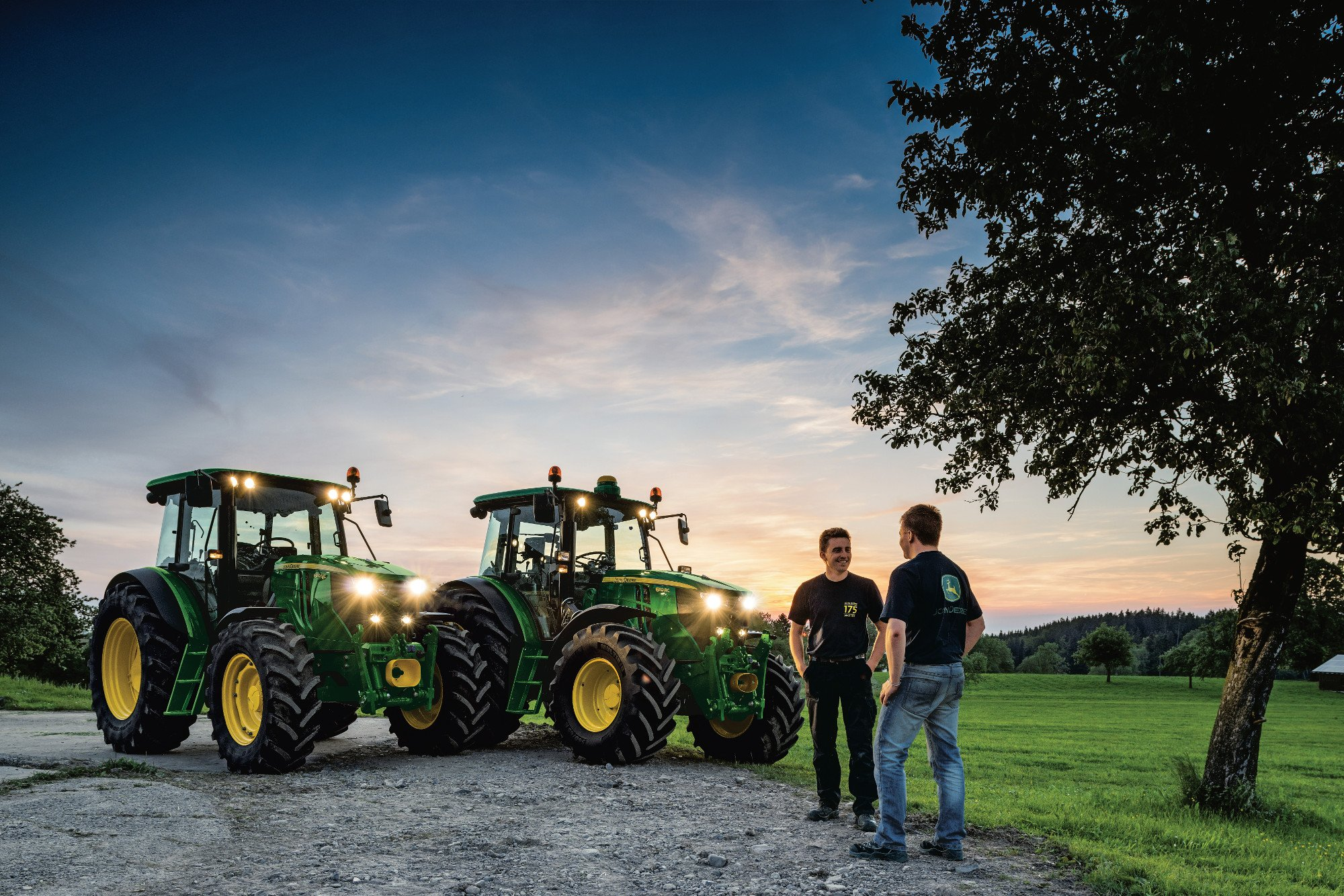 Two men talking next to a couple of John Deere tractors