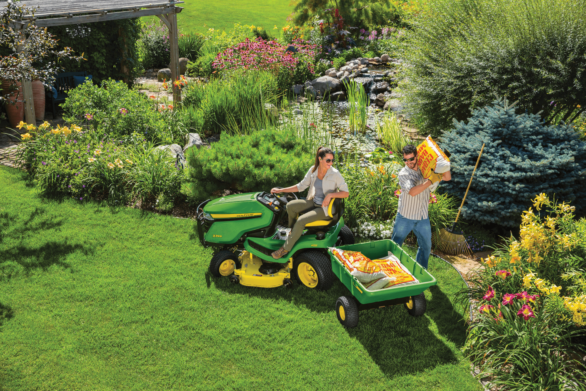 Man driving a John Deere lawn mower with pull behind trailer