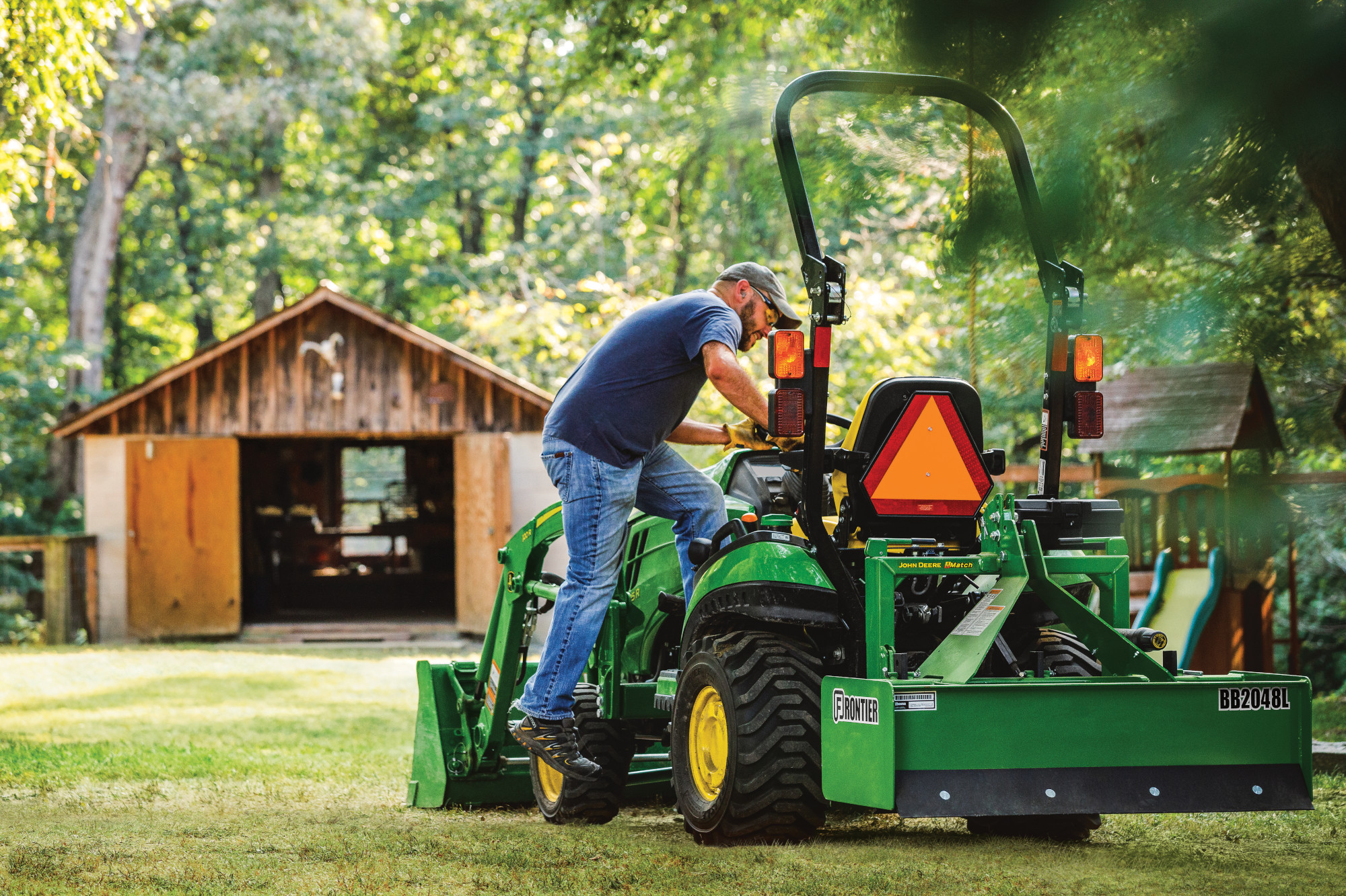 Man getting onto John Deere compact utility tractor